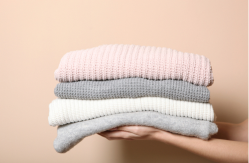 hands holding stack of sweaters