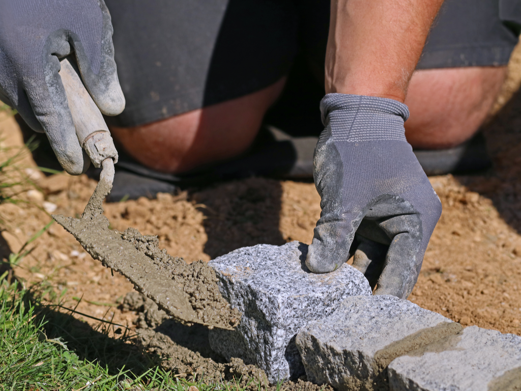Close up photo of worker with trowel and gloves