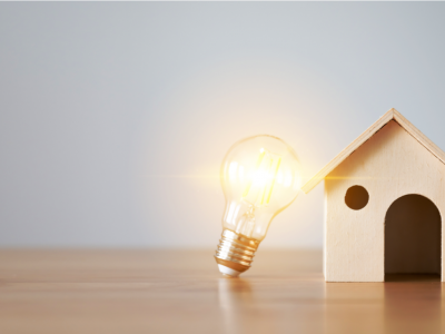 Light bulb and wooden house on the table